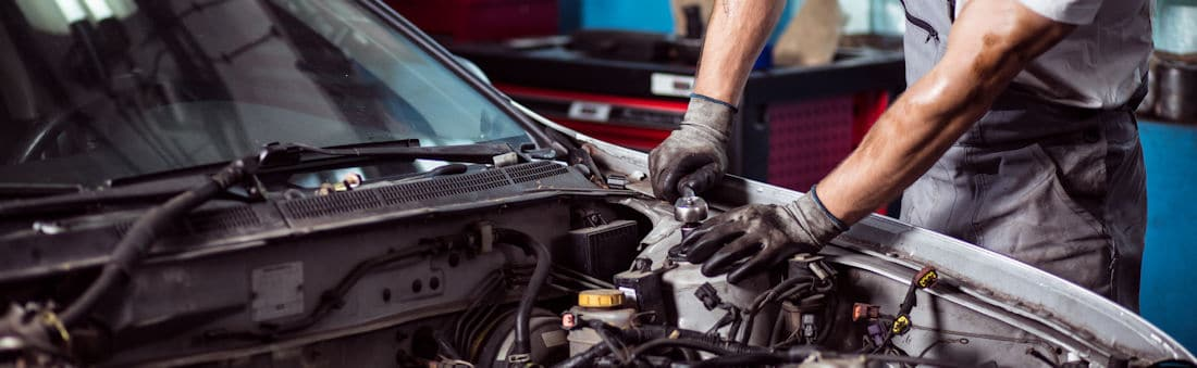auto mechanic under hood
