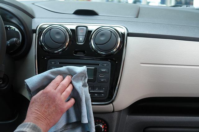 man washing a car dashboard