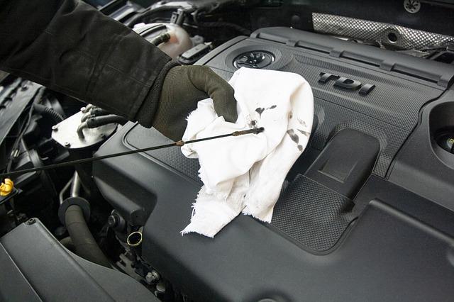 mechanic checking car oil