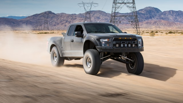 ford truck with a lift kit driving on dirt road